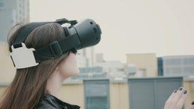 Brunettefrauenmädchen mit dem wellenartig bewegenden Haar benutzt Gläser einer virtuellen Realität auf dem Dach 4K Stockbild