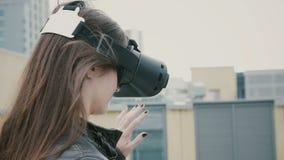 Brunettefrauenmädchen mit dem wellenartig bewegenden Haar benutzt Gläser einer virtuellen Realität auf dem Dach 4K Lizenzfreies Stockbild