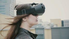Brunettefrauenmädchen mit dem wellenartig bewegenden Haar benutzt Gläser einer virtuellen Realität auf dem Dach 4K Lizenzfreie Stockfotografie