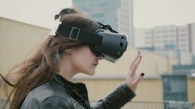 Brunettefrauenmädchen mit dem wellenartig bewegenden Haar benutzt Kopfhörer der virtuellen Realität 3D auf dem Dach 4K Stockfoto