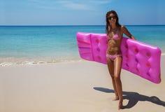 Brunettefrauensonnenbrille nimmt mit Luftmatraze auf tropischem Strand ein Sonnenbad Lizenzfreies Stockfoto