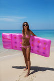 Brunettefrauensonnenbrille nimmt mit Luftmatraze auf tropischem Strand ein Sonnenbad stockfotos