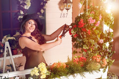 Brunettefrauenzerlegungsbetriebe mit Baumschere im Garten Lizenzfreies Stockfoto