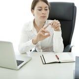 BrunetteGeschäftsfrau-Dateinägel während Arbeit Lizenzfreie Stockfotografie