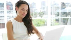 Brunettegeschäftsfrau, die auf ihrem Laptop schreibt