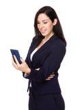 Brunettegeschäftsfrau gelesen auf Mobiltelefon stockbild
