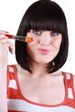 Brunetteholdingbürste zu ihrem Gesicht Stockfotos