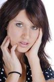 Brunetteholdinghände zum Gesicht Stockbild
