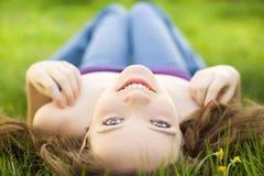 Brunettejugendlich-Mädchenlächeln auf Wiese stockfotografie