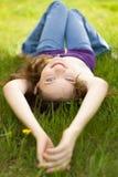 Brunettejugendlich-Mädchenlächeln auf Wiese stockbilder