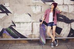 Brunettejugendliche in der Hippie-Ausstattung (kurze Jeanshose, keds, kariertes Hemd, Hut) mit einem Skateboard am Park Lizenzfreies Stockbild