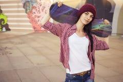 Brunettejugendliche in der Hippie-Ausstattung (kurze Jeanshose, keds, kariertes Hemd, Hut) mit einem Skateboard am Park Stockfotografie