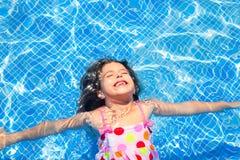 Brunettekindmädchen, das blaues Fliesepool schwimmt Lizenzfreies Stockfoto