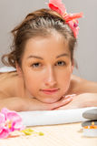 Brunettemädchen auf dem Tuch in einem Badekurort stockbild