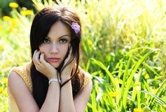 Brunettemädchen auf grünem Gras am Sommerpark. Porträt der jungen Schönheit Lizenzfreies Stockbild