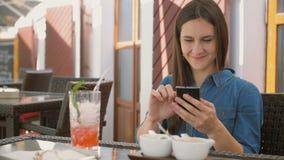 Brunettemädchen benutzt intelligentes Telefon, beim Sitzen draußen in einem Café, lächelt und lacht 4k, Lizenzfreies Stockbild