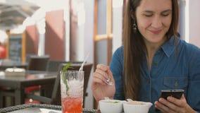 Brunettemädchen benutzt intelligentes Telefon beim Sitzen draußen in einem Café und isst Eiscreme 4k, Lizenzfreies Stockfoto