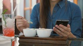 Brunettemädchen benutzt intelligentes Telefon beim Sitzen draußen in einem Café und isst Eiscreme 4k, Stockbilder