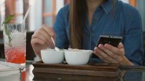 Brunettemädchen benutzt intelligentes Telefon beim Sitzen draußen in einem Café und isst Eiscreme 4k, Lizenzfreie Stockfotos