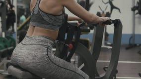 Brunettemädchen, das Übung im Blocksimulator tut Eignungsmädchen in der grauen Sportkleidung stock video footage