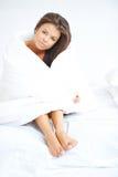 Brunettemädchen, das auf dem Bett eingewickelt in der Steppdecke sitzt Lizenzfreies Stockbild