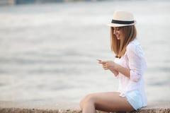 Brunettemädchen, das auf dem Strand mit Telefon sich entspannt Stockfotografie