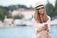 Brunettemädchen, das auf dem Strand mit Telefon sich entspannt Lizenzfreies Stockfoto