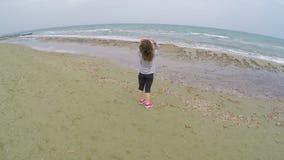 Brunettemädchen, das auf dem Strand steht und kühle Ansicht über Meer, Entspannung genießt stock video