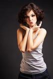 Brunettemädchen, das auf dunklem Hintergrund aufwirft lizenzfreies stockfoto