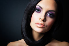 Brunettemädchen, das auf dunklem Hintergrund aufwirft Stockfotografie