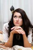 Brunettemädchen, das auf Sofa liegt Lizenzfreie Stockfotografie