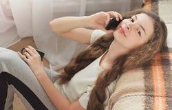 Brunettemädchen, das auf Teppich nahe Sofa sitzt und telefonisch, horizontal spricht Lizenzfreie Stockbilder