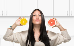 Brunettemädchen, das eine Zitrusfrucht in der Küche hält Stockfoto