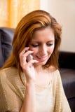 Brunettemädchen, das am Grundtelephonieren sitzt Stockbild