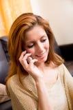 Brunettemädchen, das am Grundtelephonieren sitzt Stockbilder