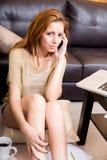 Brunettemädchen, das am Grundtelephonieren sitzt Lizenzfreies Stockbild
