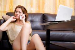 Brunettemädchen, das am Grundtelephonieren sitzt lizenzfreies stockfoto