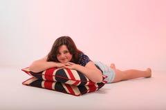 Brunettemädchen, das Kissen umarmt Stockbilder