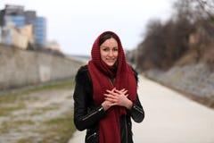 Brunettemädchen, das schwarze Lederjacke mit einem roten Schal trägt stockbild