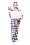 Brunettemädchen in den Pyjamas, die ein Plakat halten und Warnung cloc zeigen stockfoto