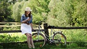 Brunettemädchen in einem Hut benutzt einen Smartphone draußen stock video