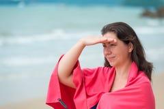 Brunettemädchen in einem rosa Tuch auf dem Strand lizenzfreies stockfoto