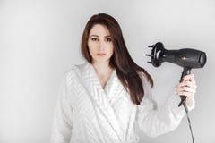 Brunettemädchen im Bademantel mit Haartrockner trocknet ihr Haar gegen einen weißen Hintergrund lizenzfreie stockfotos