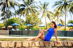 Brunettemädchen im Blau sitzt auf Steinsperre gegen Pool Lizenzfreie Stockfotografie