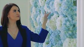 Brunettemädchen im blauen Gehen nahe bei Blumenwandzeitlupe stock footage