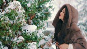 Brunettemädchen im braunen Pelzmantel bürstet das Gehen in Winterzeitzeitlupe stock video footage