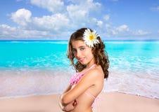 Brunettemädchen im tropischen Strand mit der Gänseblümchenblume glücklich Lizenzfreie Stockfotografie