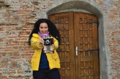 Brunettemädchen mit alter Fotokamera auf dem Film, Fotos machend Lizenzfreie Stockfotos