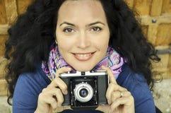 Brunettemädchen mit alter Fotokamera auf dem Film, Fotos machend Stockfoto