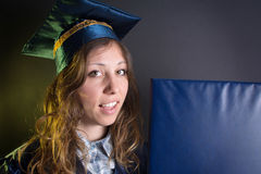 Brunettemädchen mit einem Diplom im Staffelungskostüm Lizenzfreies Stockbild